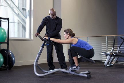 Precor_In-Club_Image_240i_StretchTrainer_01_Female_demonstrating_lower_back_stretch_with_male_trainer_01_8